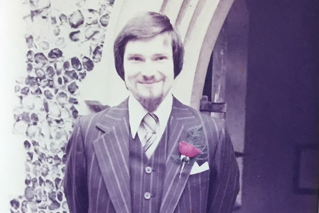 An old photo of a man dressed in a brown suit outside a church.