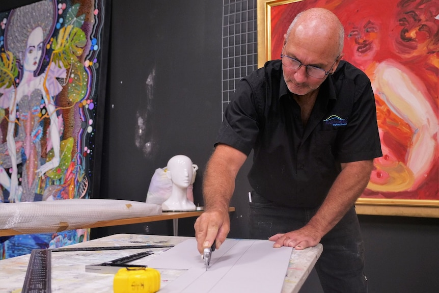 A bald man wearing a black shirt and spectacles, cuts a piece of cardboard with a knife, with colourful artworks behind.