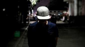 A man stands with his face down in a dark alleyway in Jakarta.