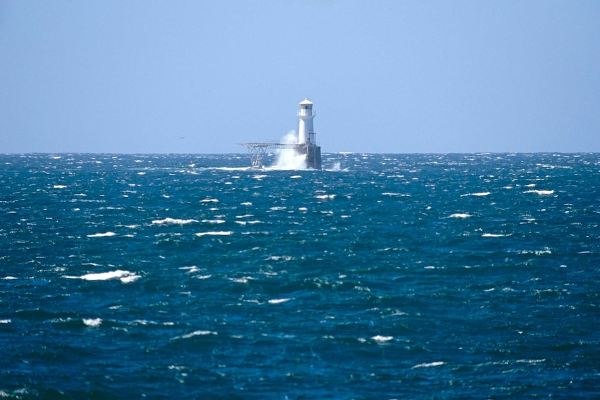 A lighthouse surrounded by whitecapped ocean.