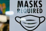 A white sign with black text reads 'MASKS REQUIRED' with an image of a mask.