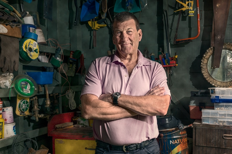 A man stands in a shed surrounded by tools.