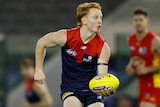 A Melbourne Demons AFL player prepares to handball to his left against the Gold Coast Suns.