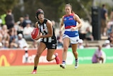 An AFLW player wearing headgear looks up as she runs with the ball as an opponent chases her.