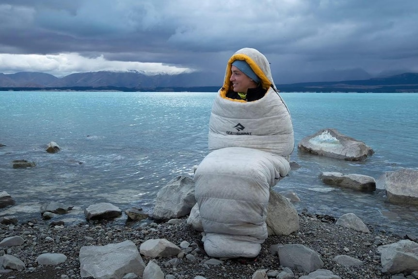 An athlete keeps warm wrapped in a sleeping bag during an ultra-marathon