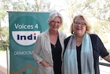 Two women with glasses and fair hair stand next to a green banner that says 'Voices 4 Indi'.