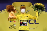 A cyclist wearing yellow stands on the podium carrying a toy lion and a bouquet