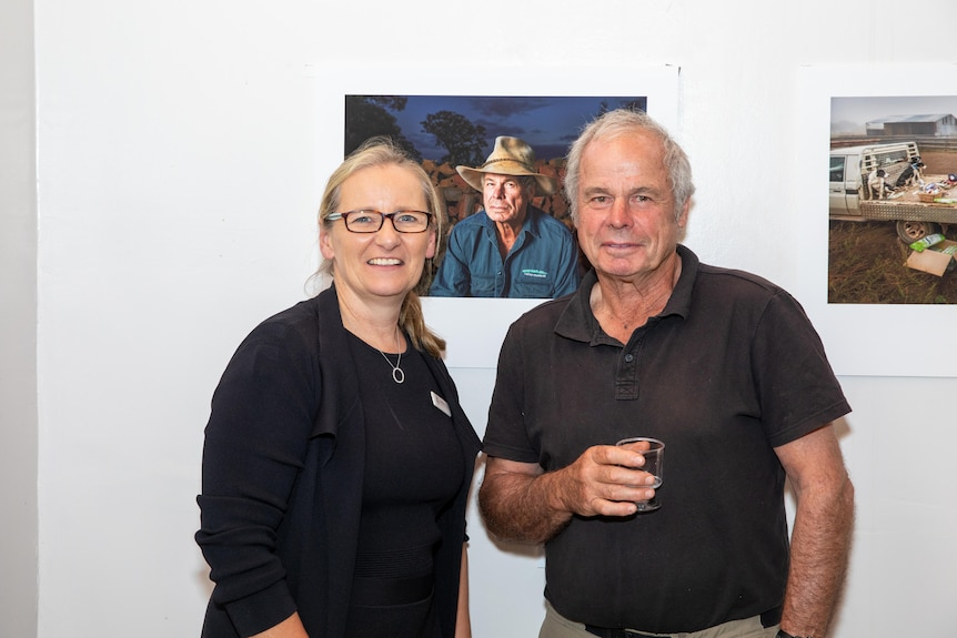 A woman and man stand side by side inside an art gallery