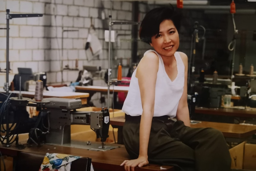 A young woman in a white sleeveless top poses sitting on the sewing machine table inside a garment factory.