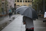 A commuter in Sydney this morning cowering from the rain.