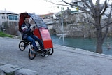 A man rolls downhill in a small red folding car.