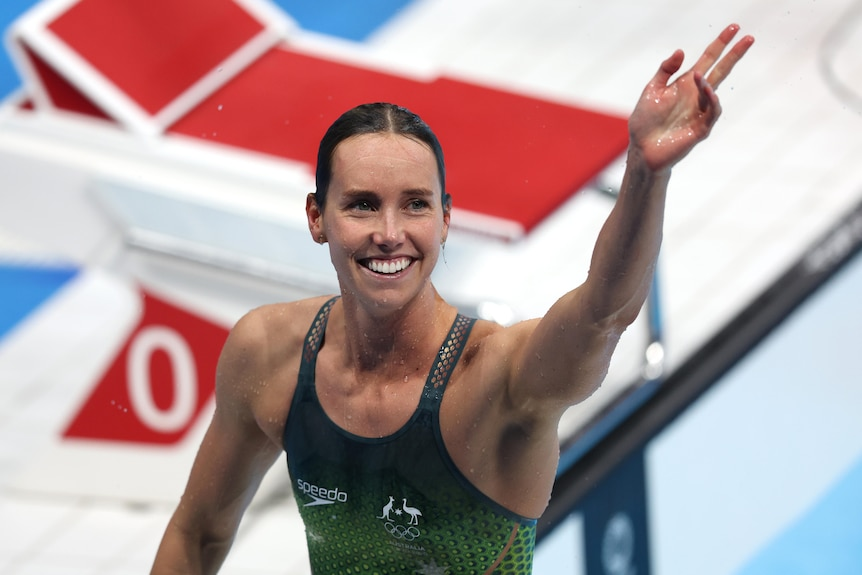 A smiling Emma McKeon of Australia waves on pooldeck after winning an Olympic gold medal in the 100m freestyle.