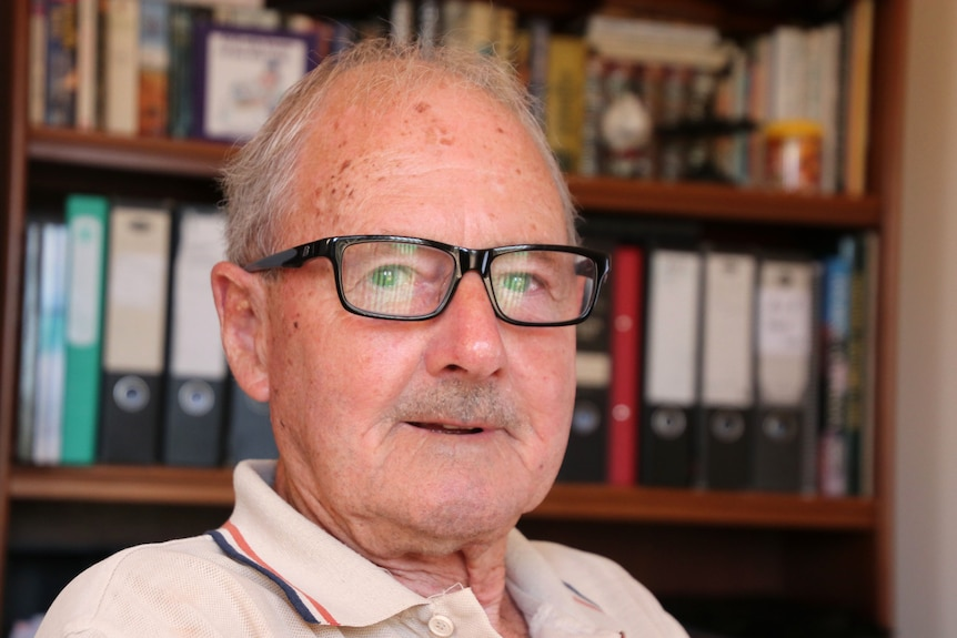 Head shot of an older man wearing glasses staring at camera with a bookshelf behind him.