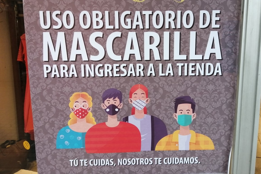 A sign in Spanish alerts customers to a store's mandatory mask policy.