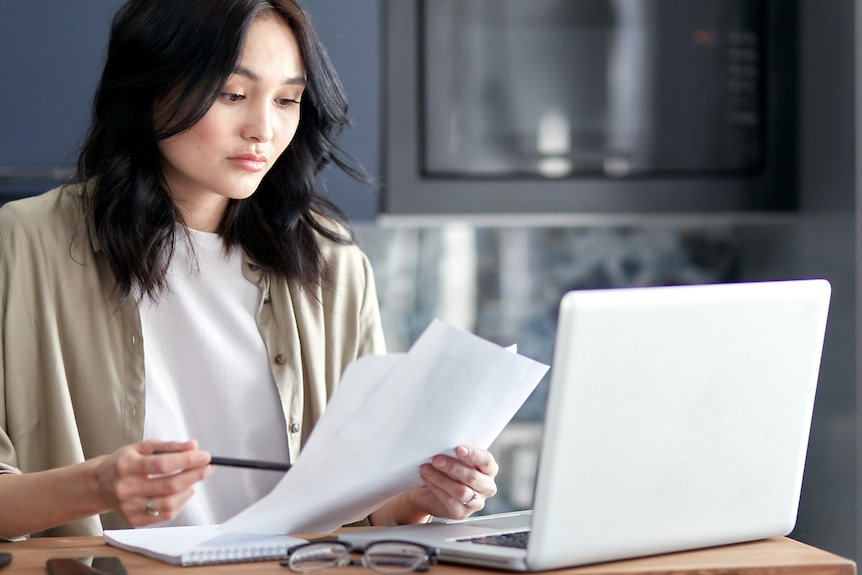 A woman with a confused look holds papers while looking at a laptop.