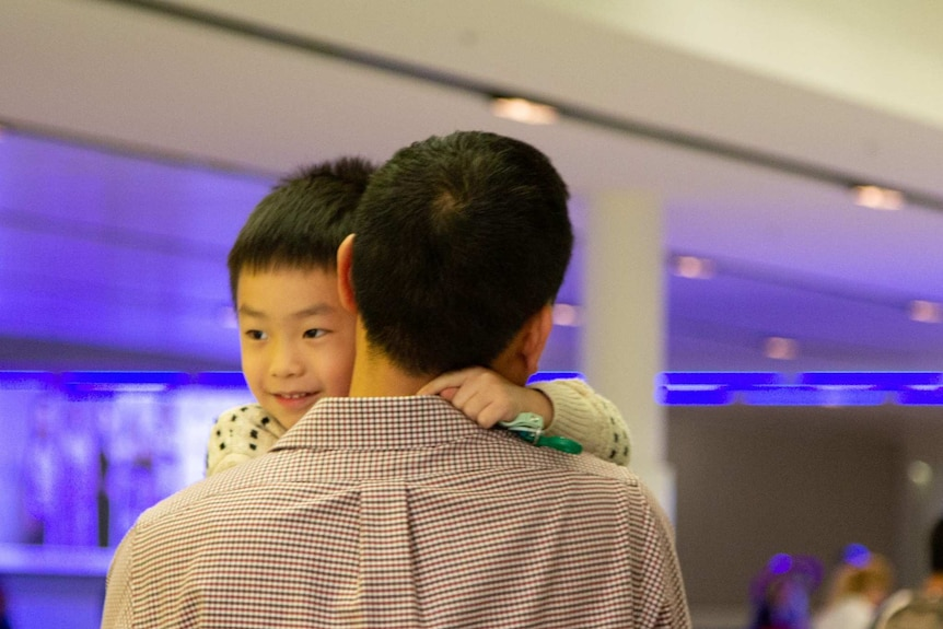Harley hugs his dad and smiles widely.