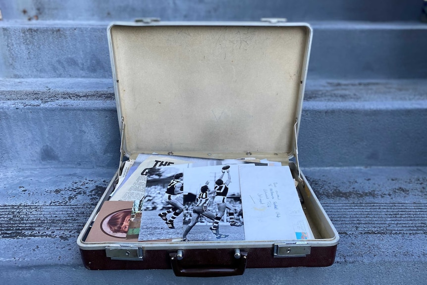 An open briefcase sits on a set of concrete stairs, displaying photographs of Rod Owen during his playing days.