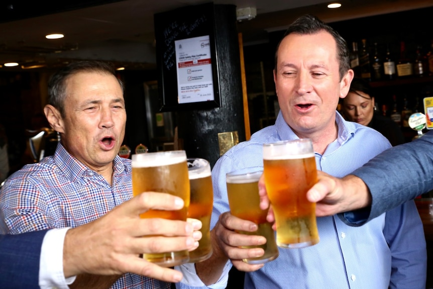 Two men holding pints of beer make a 'cheers' gesture with other people at a pub.