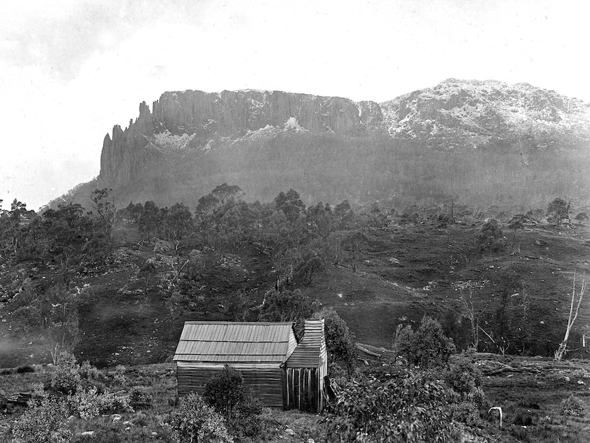 A rustic hut in the foreground with a large mountain in the background