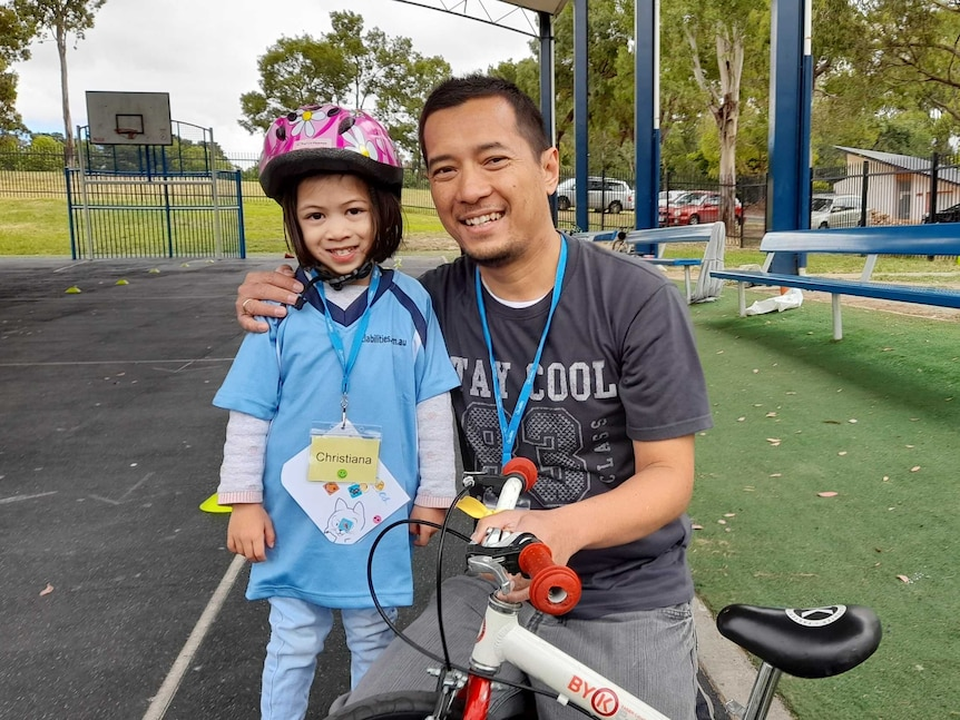 A girl wearing a bike helmet smiles next to her bike and her dad.