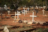 Crosses and flowers mark graves in the dirt at Broome cemetery.