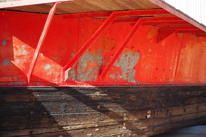 A weathered-looking barge with a rusty and peeling red hull.