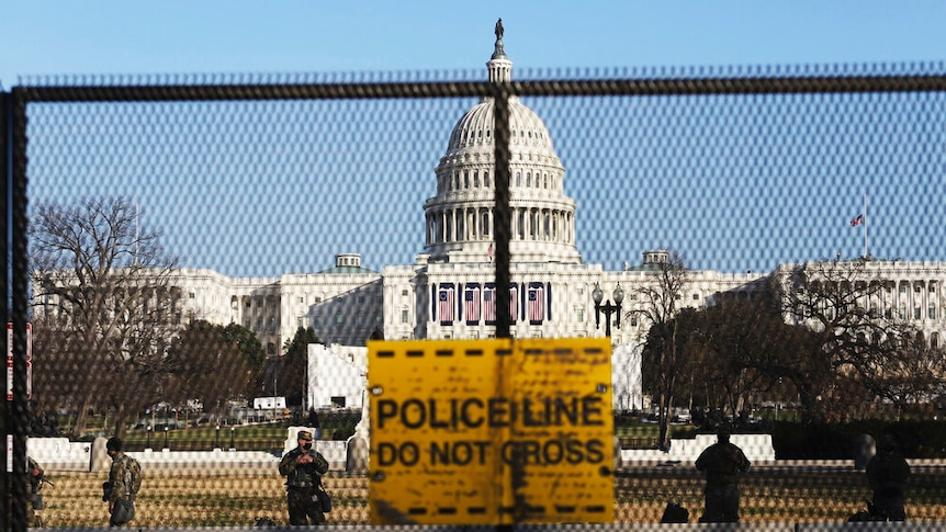 National guards are seen behind a fence that was erected to reinforce security at the Capitol in Washington.