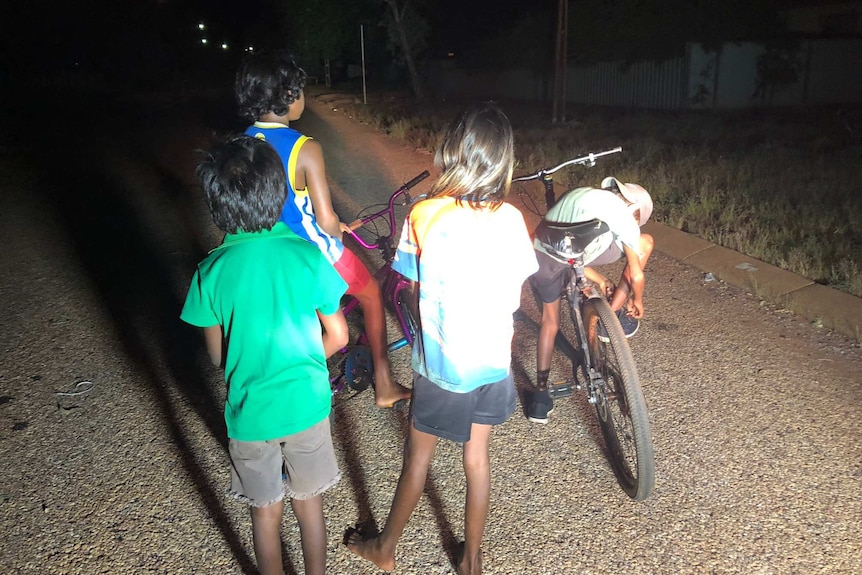 A photo of four children playing on their bikes in the street at night.