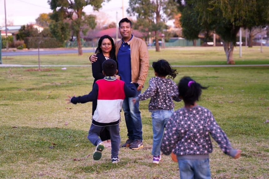 A man his wife smile at the camera while three children run towards them