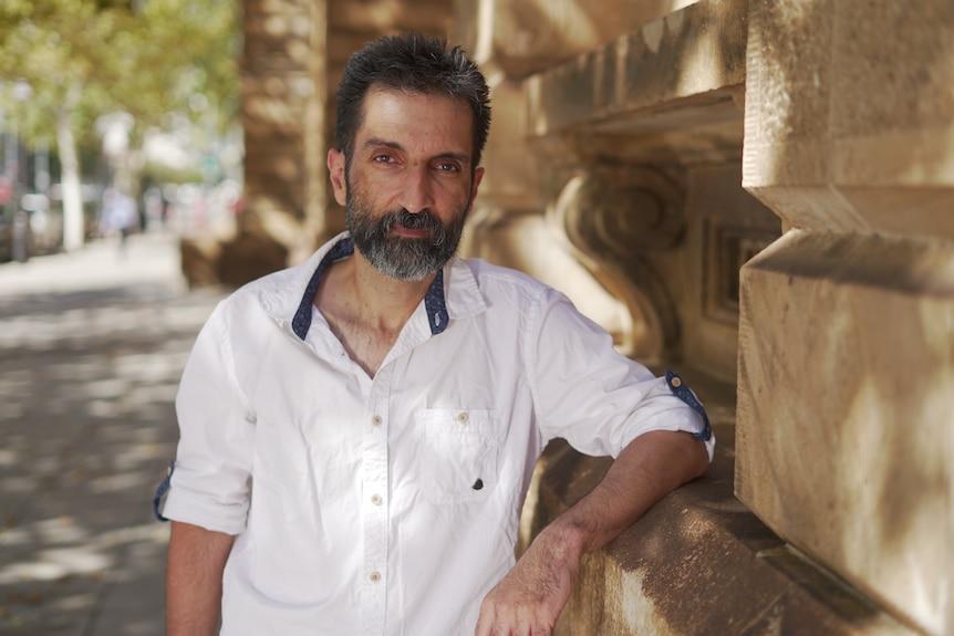 A man with a beard wearing a white shirt