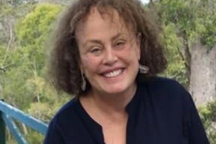 Judith Fordham smiles for a photo outdoors wearing a black top.