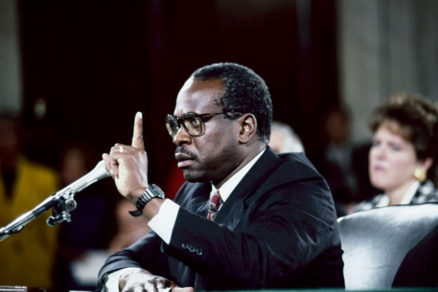 An old photograph of Clarence Thomas with his hand in the air