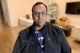 A man in glasses looks at the camera.