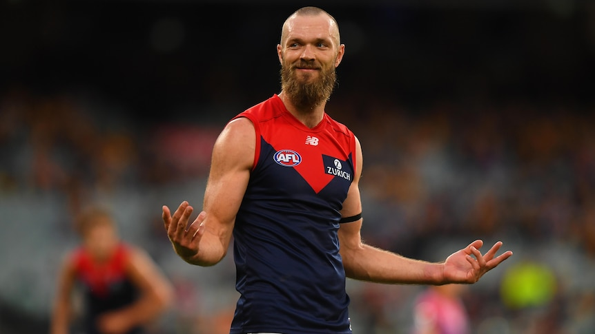 A Melbourne Demons AFL player smiles as he stands with his arms held out to his sides after kicking a goal.
