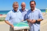 Bill Marmion, Sean L'Estrange and Joe Francis with a picture of a shark deterrent system.