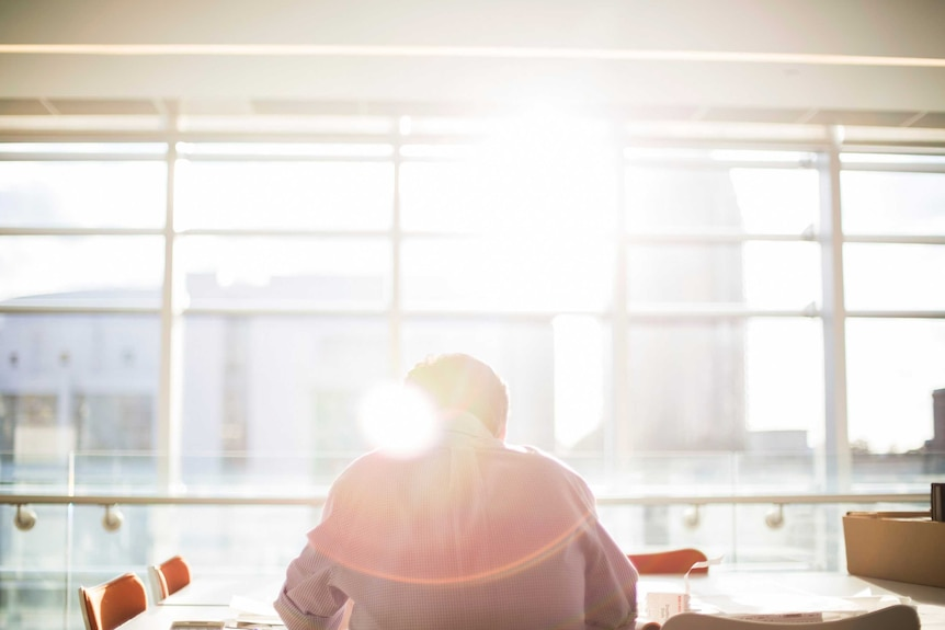 Man sitting in empty sunlit meeting room, depicting the stress and isolation that mismanaged workplace mental health can create.