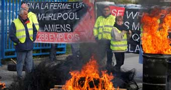 Whirlpool employees with signs and burning tyres in protest against French economy