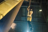 A protester scales down a rope hanging from the side of a bridge with a dim green light lighting him up at night.