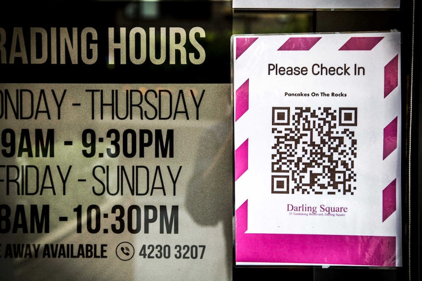 signage of restaurant opening times next to a pink QR code