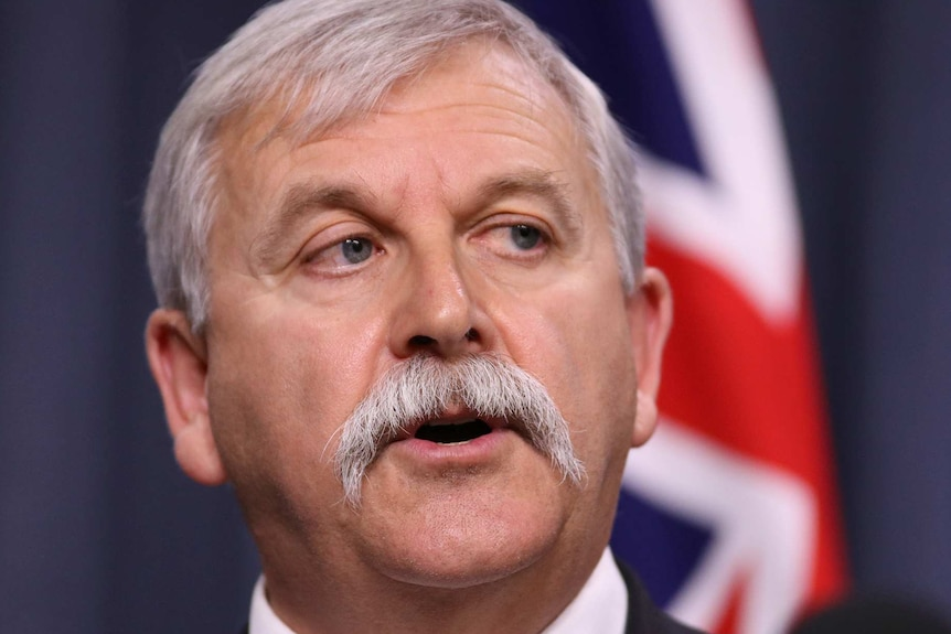 A man with grey hair and a moustache at a press conference in front of an Australian flag.