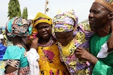 A released Chibok girl embraces her parents, her mother's face is covered in tears. They are all brightly dressed.