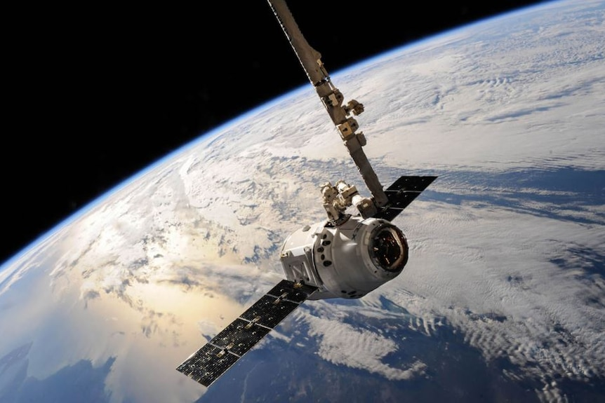 A satellite in space with Earth in the background.