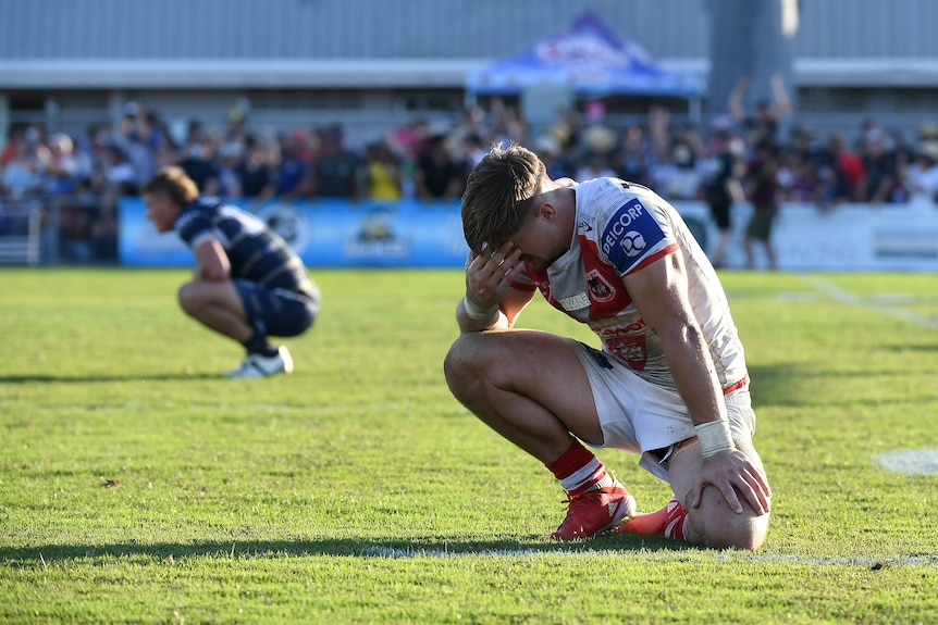 A St George Illawarra Dragons NRL player kneels as he reflects on his side's loss to the Cowboys.