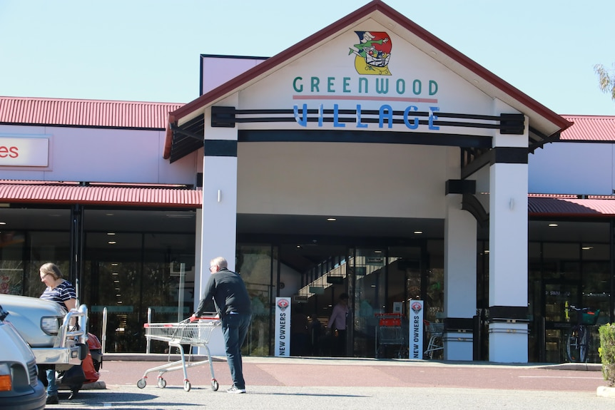 The front entrance to Greenwood Village Shopping Centre with shoppers in the car park.