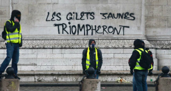 Demonstrators stand by graffiti at the base of the Arc de Triomphe.