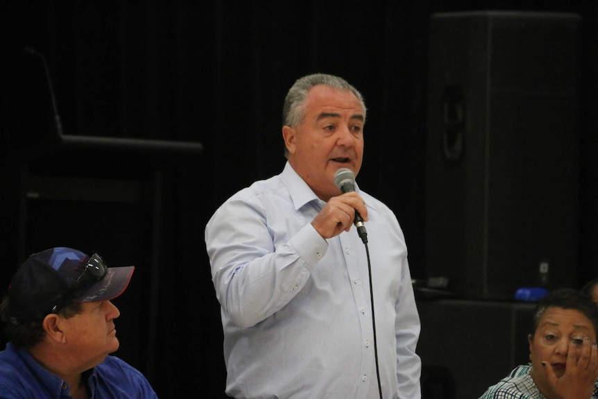 Gerry McCarthy standing with a microphone and speaking on a panel.