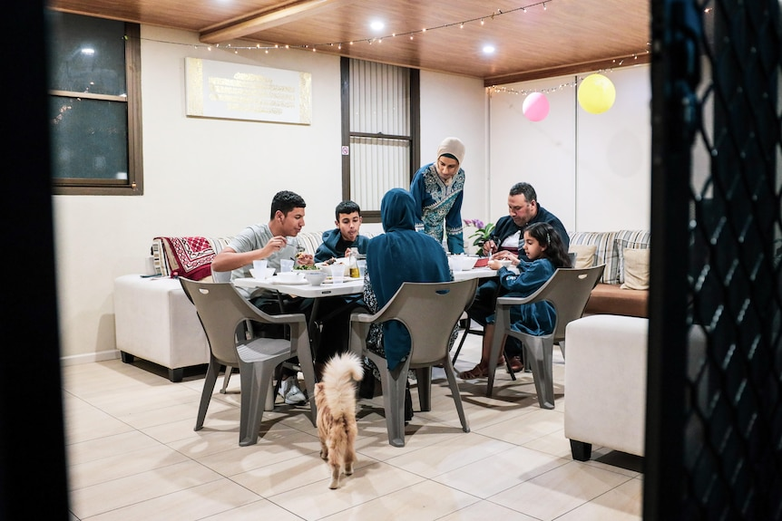 people sitting on chairs around a table eating