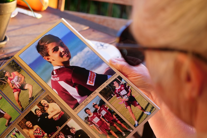 A woman with blond hair wearing sun glasses looks at a photo of a boy wearing maroon jersey