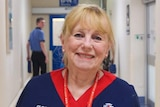 A nurse poses for a photo smiling in a corridor at Royal Perth Hospital.