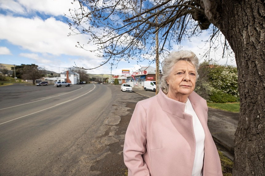 Ms Triffit stands by the side of the empty Lyell Highway in Ouse. She is wearing a pink jacket.